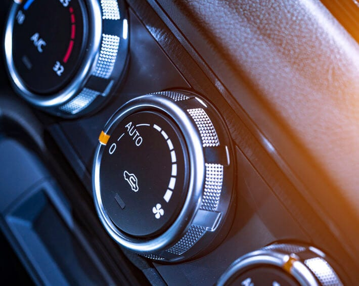 Three knobs on car air conditioner with sun streaming in at top right corner