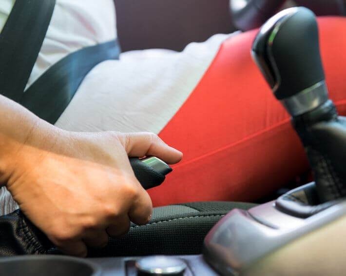 Woman in red pants pulling parking brake in car after brake failure