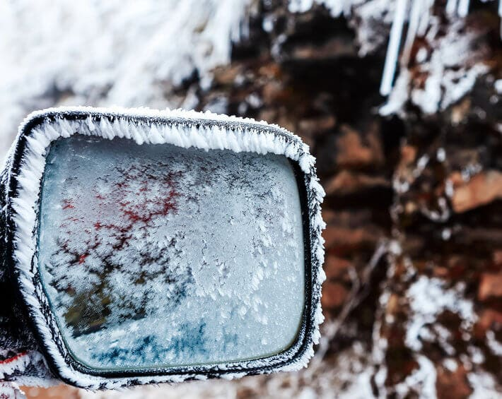 Frosted car mirror on cold winter morning