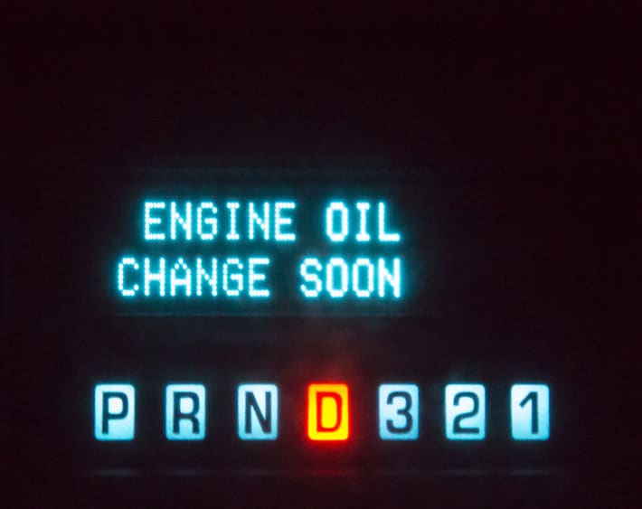"""Lights on a car dashboard at night that says """"Engine oil change soon"""". The words are in blue. The symbols for what gear the automobile is in is also lit. The letter D is orange, showing that the vehicle is in drive."""