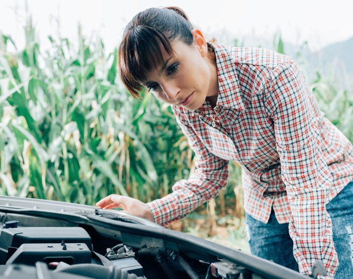 Woman with her ear tilted towards her car's engine, listening for what the car noise might be