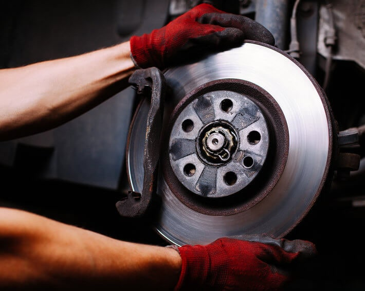 Firestone Complete Auto Care technician's red gloved hands performing a brake repair service