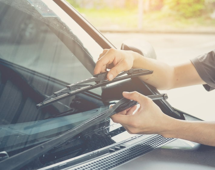 Hand picking up windscreen wiper on car and checking rubber, checking to see whether wipers need to be replaced