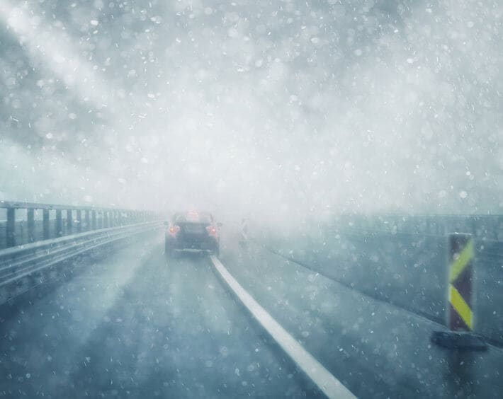 Car driving in winter weather, limited visual distance, and snow falling on roadway