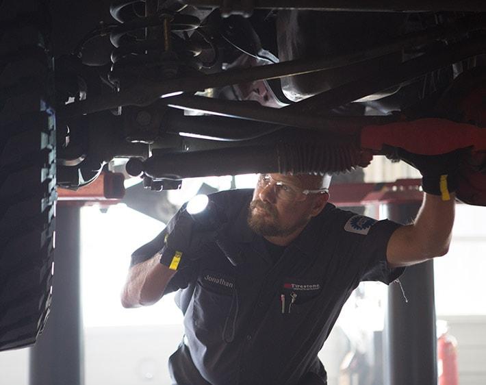 Firestone Complete Auto Care technician examining undercarriage of car