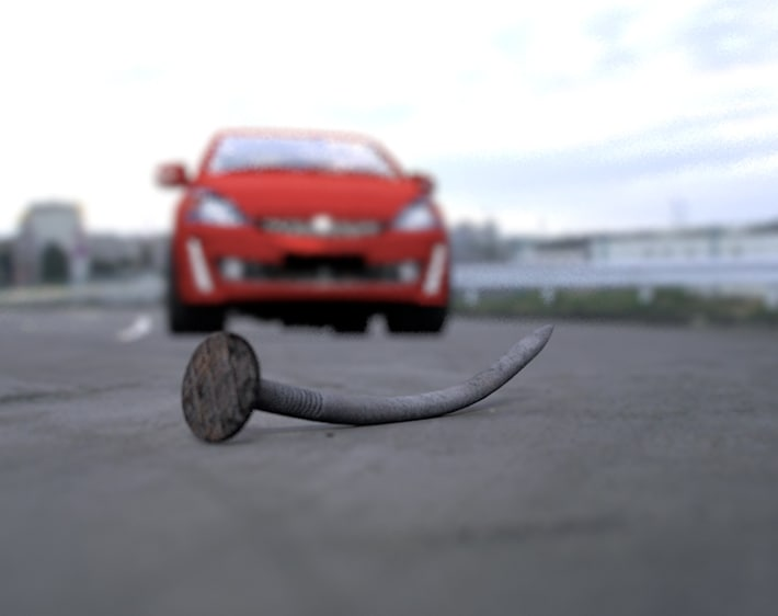 Red car approaching nail in road, safe driving tips from Firestone Complete Auto Care
