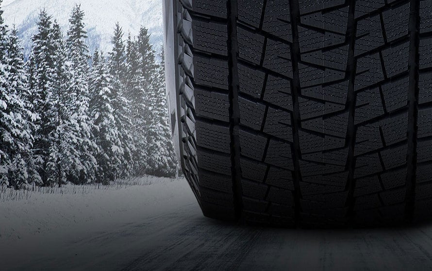 Close up of Bridgestone's Blizzak winter tire, going down a snowy road with snow-capped trees ahead