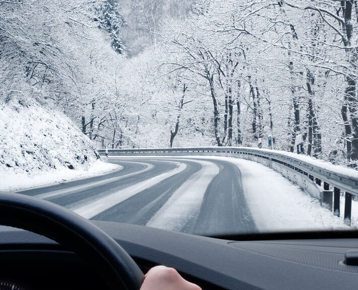 Driver's hands gripping steering wheel on snowy road, surrounded by snow covered trees