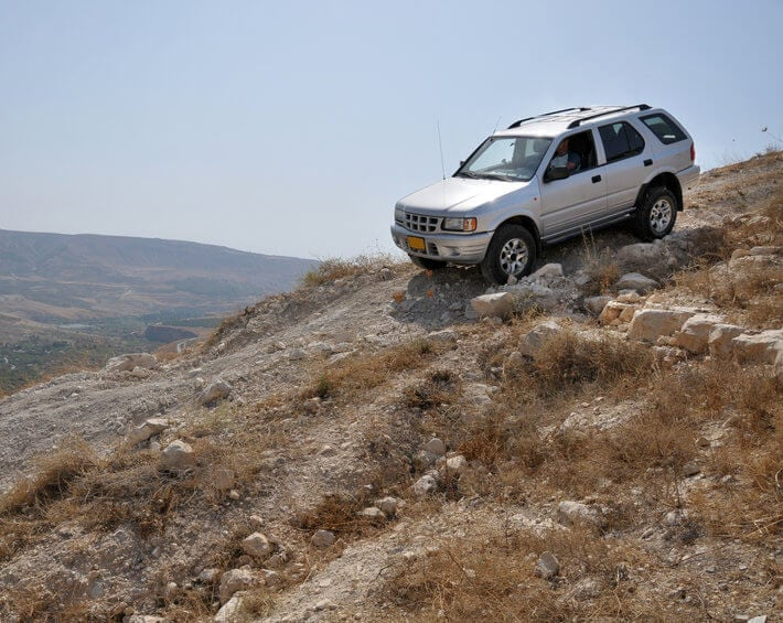 Silver SUV off-roading in mountainous, dry climate