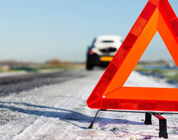 Close up of orange hazard triangle on snowy road, car in background