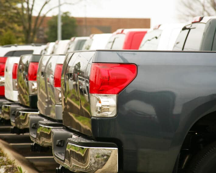 Row of new trucks for sale, with focus on the bed of the trucks