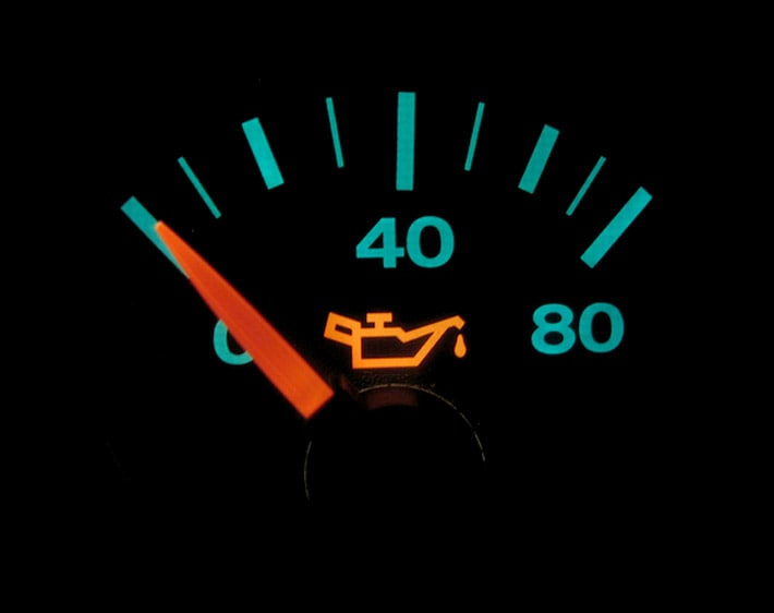 Close up of oil pressure gauge on car dashboard, with gauge reading at low level