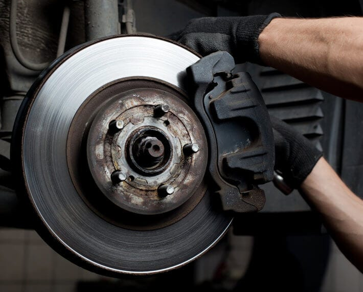 Close up of car's rotor with brake pad and mechanic's hands working