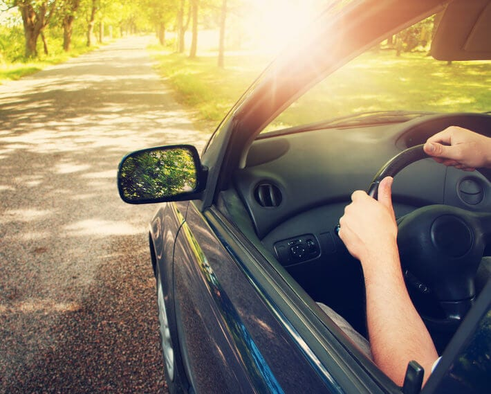 Driver's hands on steering wheel, with driver headed down asphalt road on bright sunny day