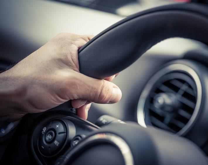Hand gripping car's steering wheel