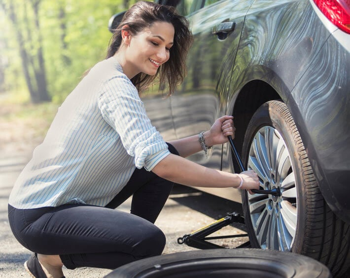 Woman replacing flat tire with spare tire