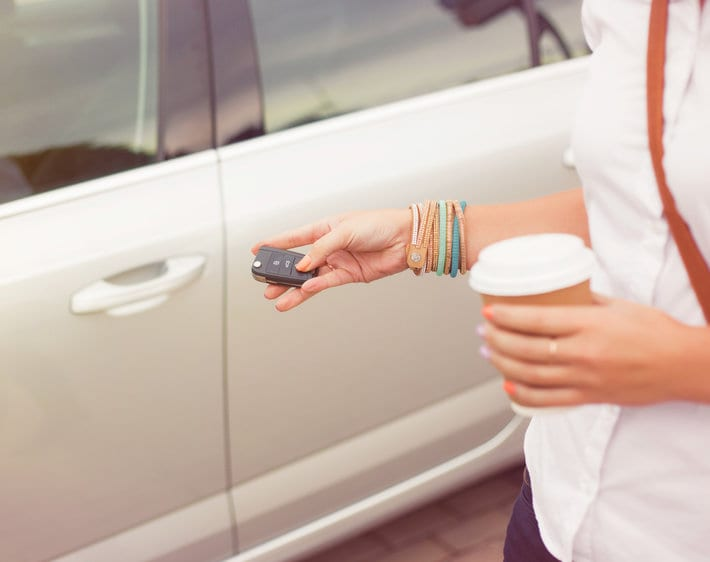 Woman opening car with keys while holding coffee