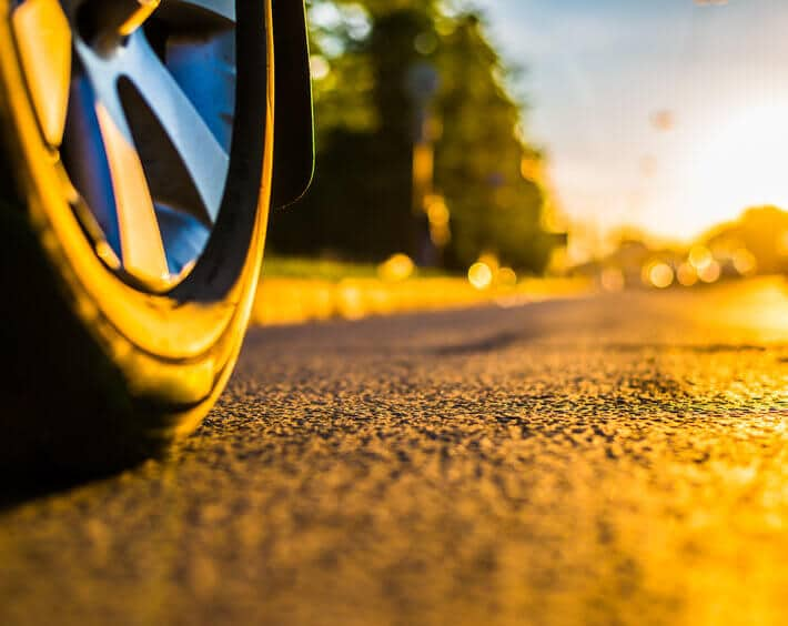 Tire on hot summer pavement, headed into the sunset