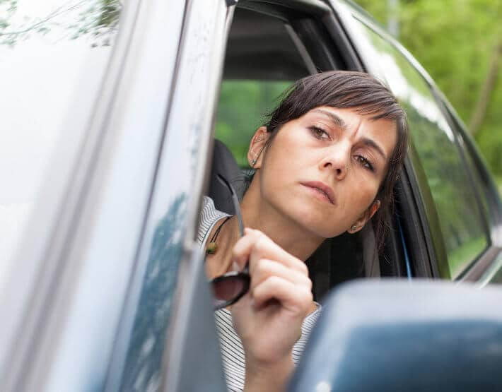 Driver concerned about bad shock symptoms, looking out her window