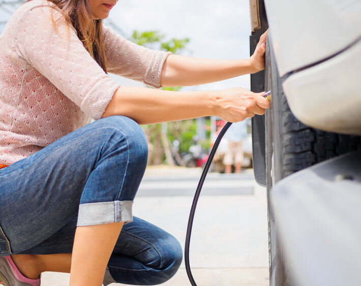 Woman in pink sweater kneeling next to her car tire, filling up tire with air