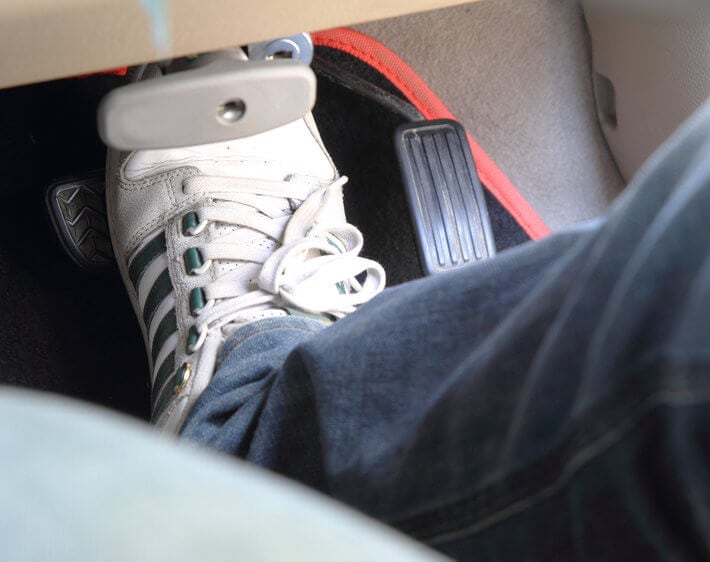 Sneakered foot pressing down on car's brake pedal