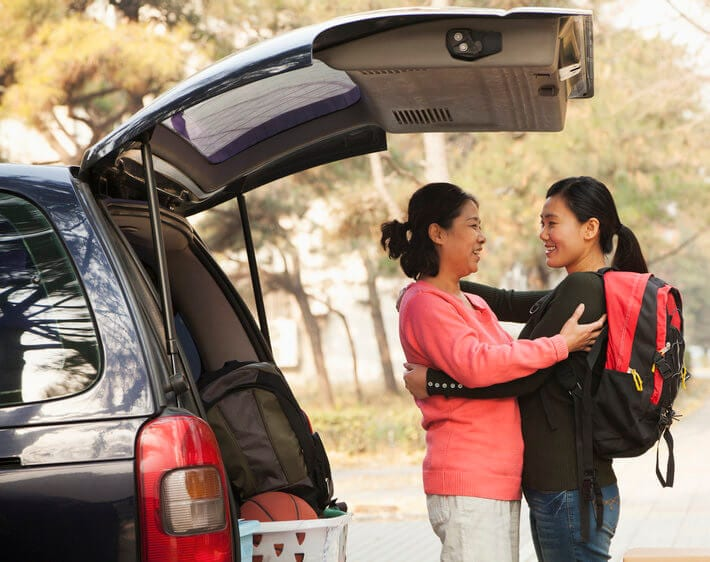 Mother and daughter hug goodbye outside of their car as daughter leaves for college