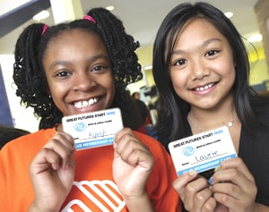 Two girls in Boys and Girls Club of America, holding up their membership cards