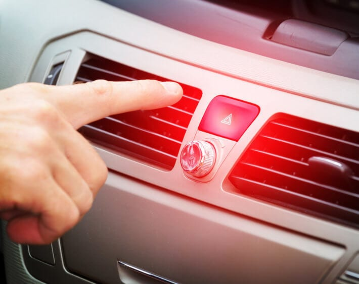 Hand reaching for car's hazard light button on center console