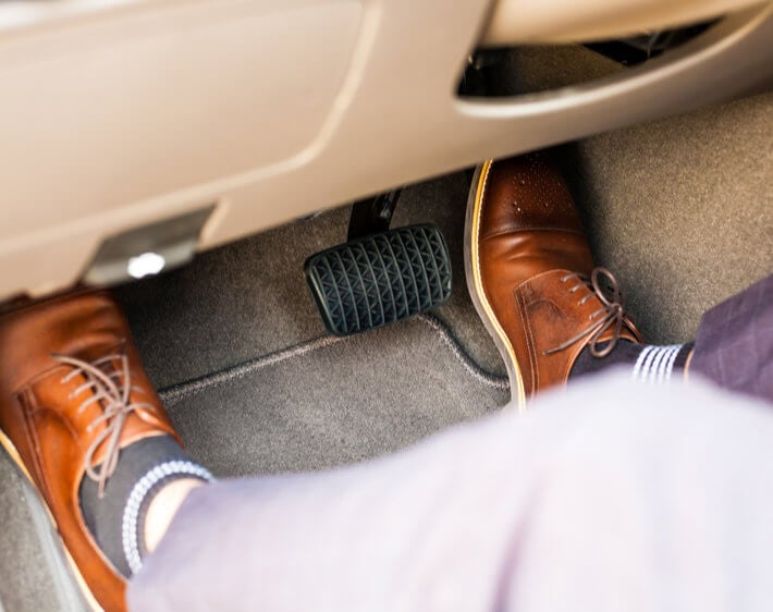 Businessman's feet in wheel well, pressing gas and brake pedal