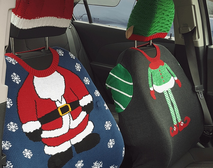 Car seats covered by festive ugly sweaters