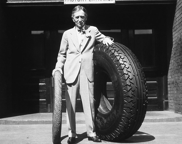Harvey S. Firestone with an original non-skid tire and an oversized tire, date unknown.