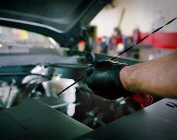 Firestone Complete Auto Care technician holding oil dipstick