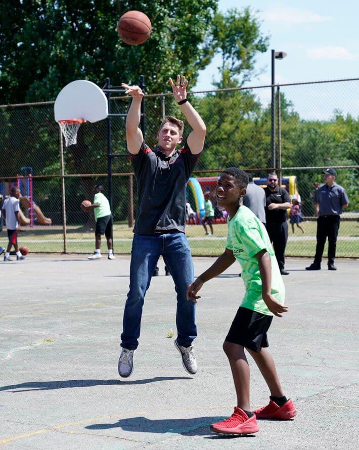Bridgestone team member shooting hoops with student