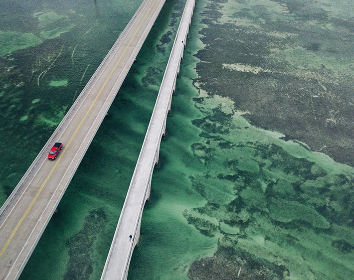red car on a highway crossing the ocean