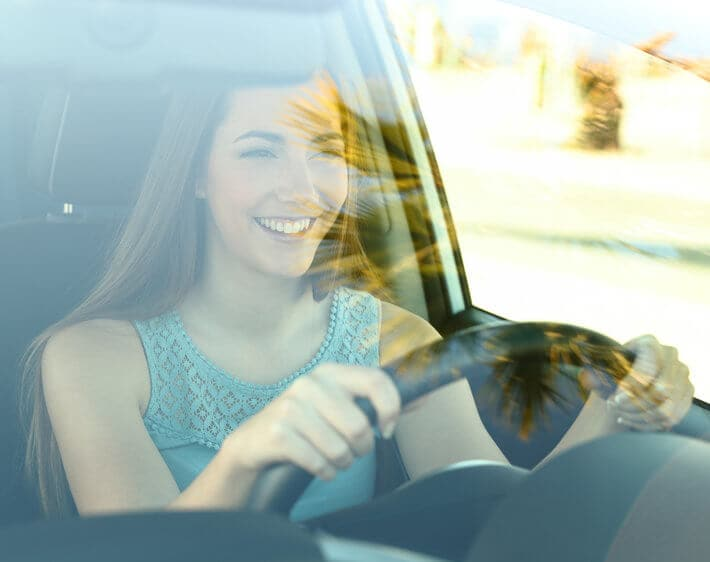 woman driving car smiling through windshield reflection