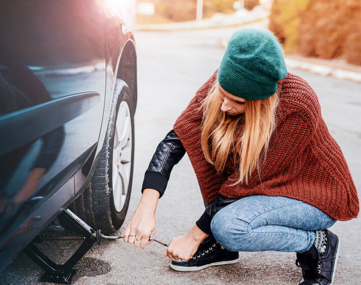woman using a jack to change a flat tire
