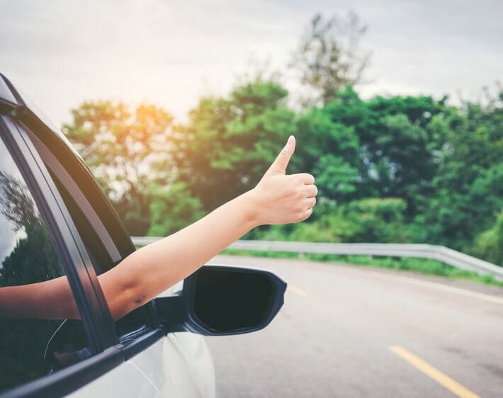 woman giving thumbs up out the window of a Toyota Camry