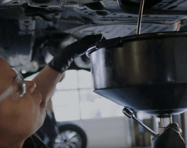Firestone technician emptying oil from a car to replace with fresh oil