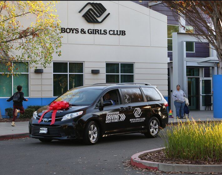 Black Bridgestone van delivered to Boys & Girls Club with a bow on top
