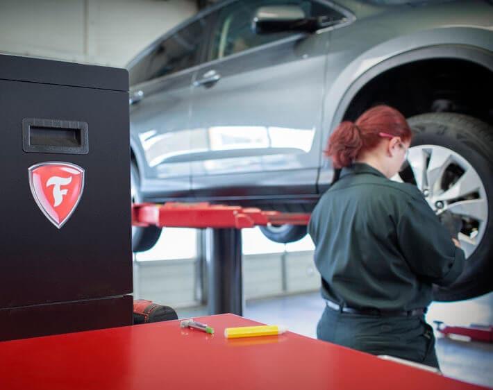 Brianna Fernando, Firestone technician, working on a car next to the Firestone logo