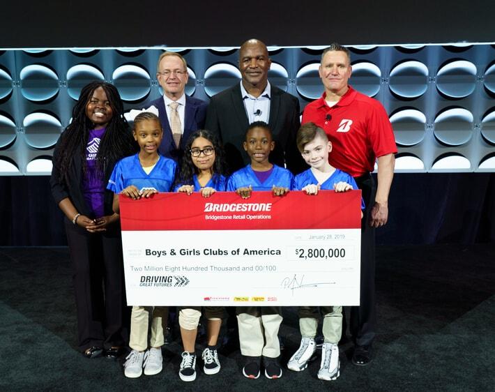 Boys & Girls Club of America receiving big donation check from Bridgestone staff