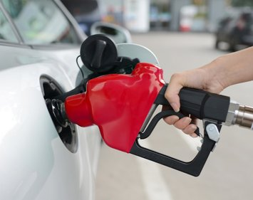 hand pumping gas refueling at gas station