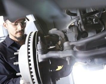 Skylar, a Firestone technician performs a brake service wearing grey overalls