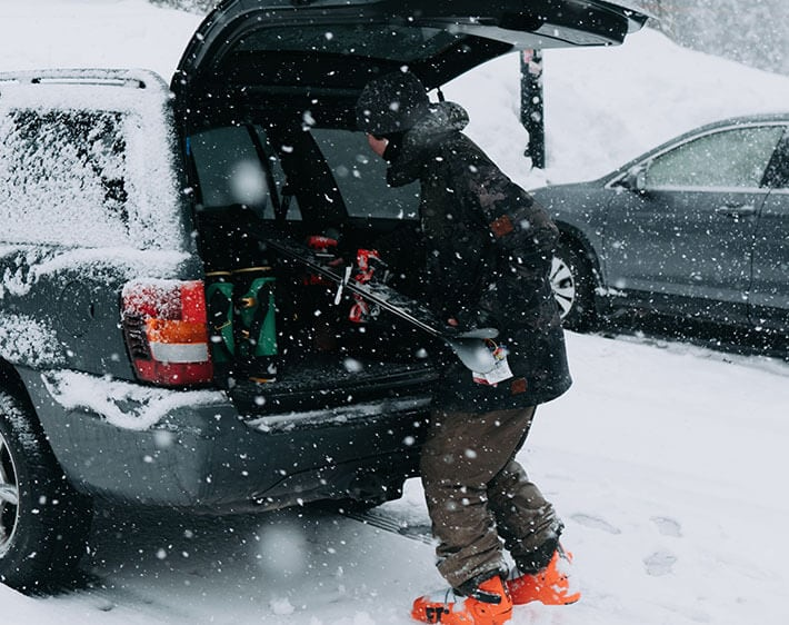 taking skis out of the trunk in the snow