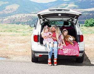 Family sitting on SUV tailgate while having fun on side of the road