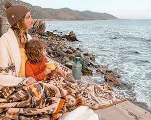 Mother and child sitting in blanket looking at the ocean