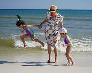 Woman in flowered dress with two girls in colorful swimsuits