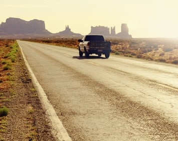 Pickup truck driving down desert road