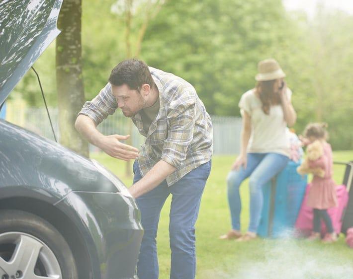Man fanning a smoking car engine