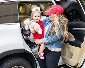 Mom holds baby in front of car